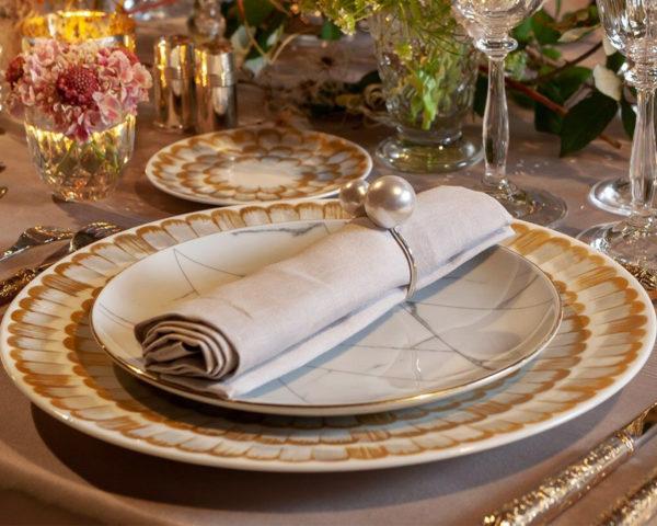 Assiette plume en blanc et doré sur table